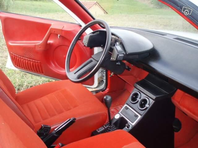 Intérieur d'une CX 2000 Super du milieu des années 70, avec l'intérieur rouge qui allait avec l'extérieur blanc : kitsch à souhait ! La nôtre avait un intérieur bleu vif tout aussi discret… On notera l'intégration dans les contreportières monobloc des gâches permettant d'ouvrir les portières, du vide-poche à soufflet et des haut-parleurs : unique à cette époque !
